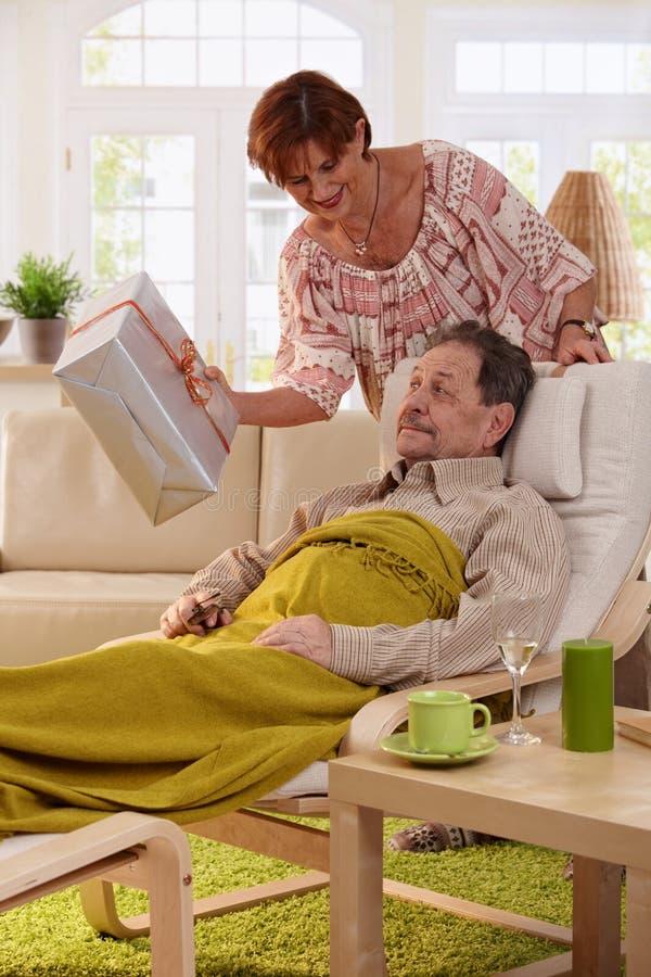 Uomo anziano che ottiene presente immagine stock