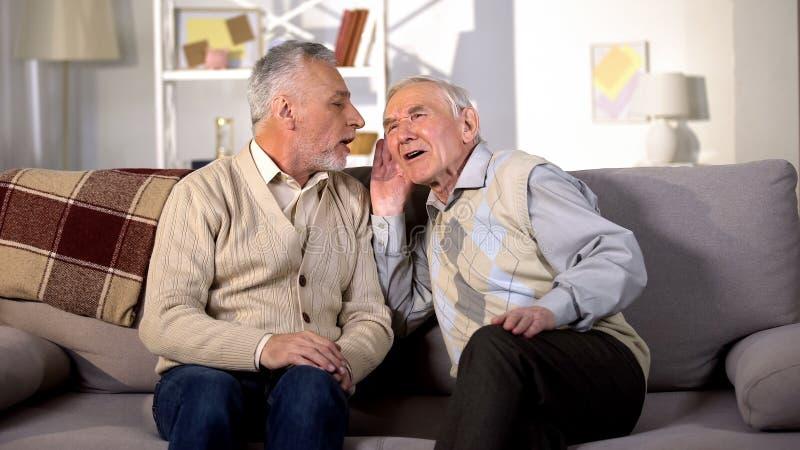 Uomo anziano che parla con un amico sordo seduto sul divano a casa, malattia dell'udito, problema immagine stock libera da diritti