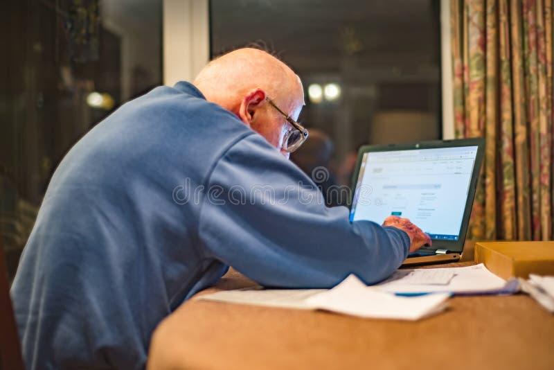 Uomo anziano che per mezzo di un computer portatile per controllare le sue cartelle di parte, Hampshire, Inghilterra, U k immagini stock