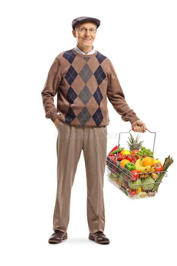 Uomo anziano che porta un cestino della spesa con la frutta e verdure e posare fotografie stock