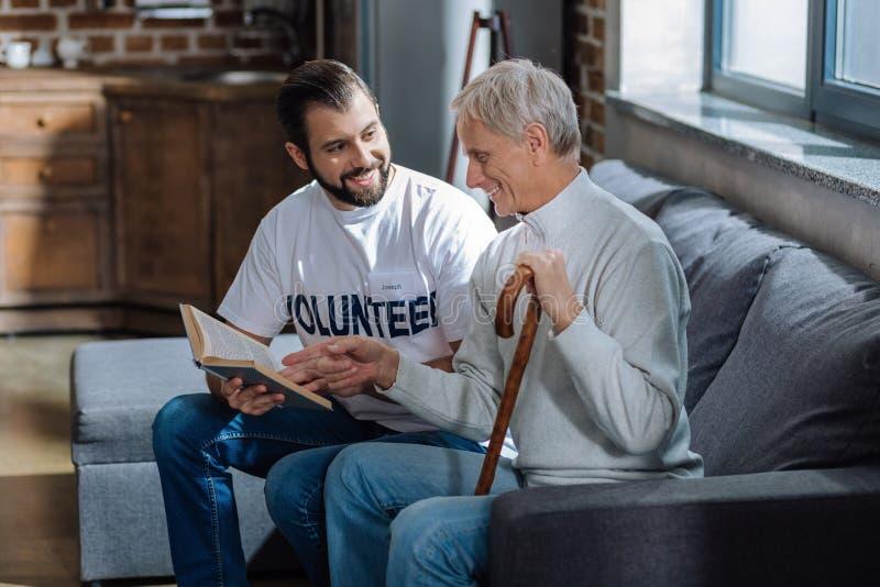 Uomo anziano che si siede con un volontario e che esamina il suo libro favorito fotografia stock libera da diritti