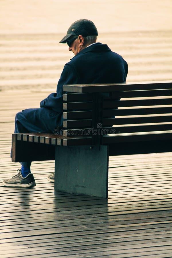 Uomo anziano che si siede da solo su un banco fotografia stock
