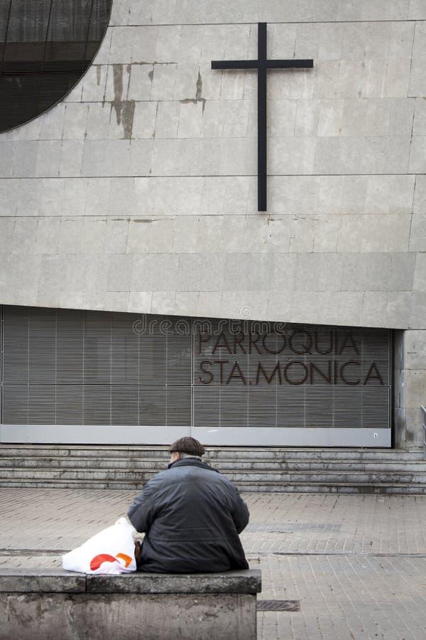 Uomo anziano che si siede nella parte anteriore una croce sulla parete della chiesa fotografie stock