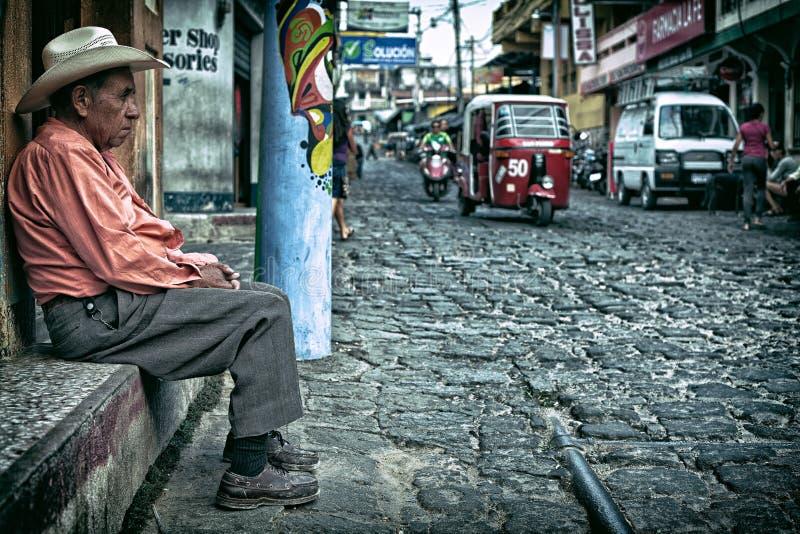 Uomo anziano che si siede su una vecchia via del ciottolo con traffico che guida vicino fotografie stock libere da diritti