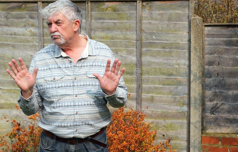 Uomo anziano che si tiene per mano dire no o fermata. fotografia stock
