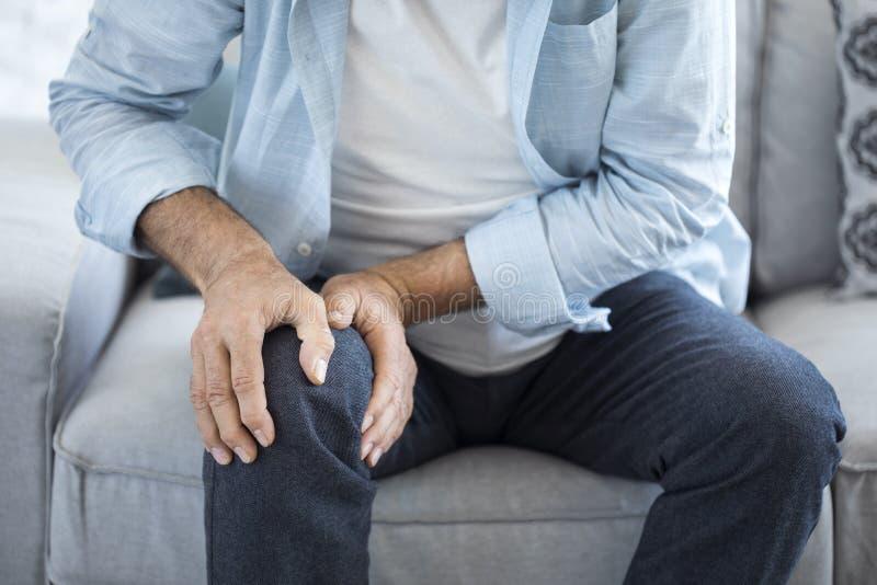 Uomo anziano che soffre dal dolore del ginocchio immagini stock libere da diritti