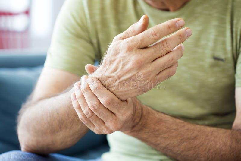 Uomo anziano che soffre dal dolore e dal reumatismo fotografia stock