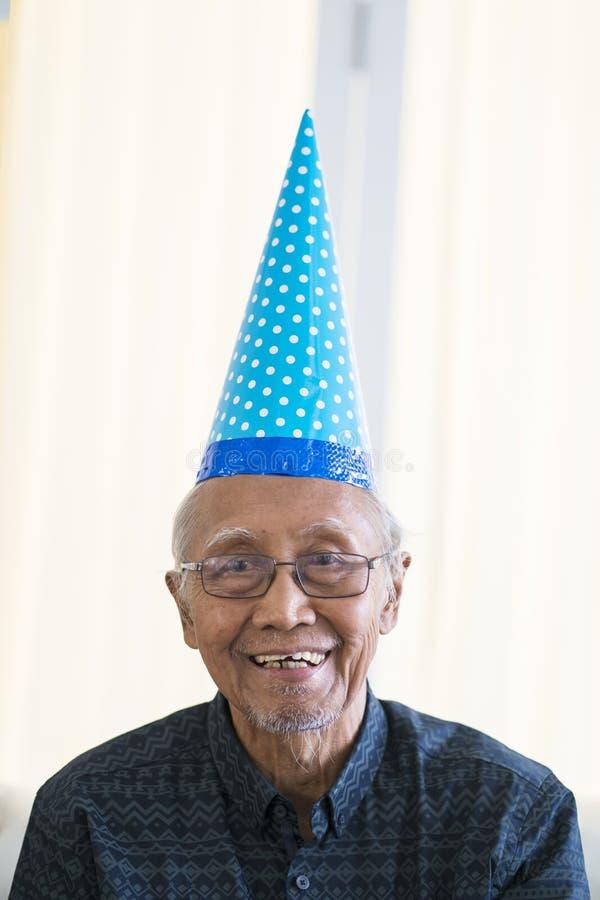 Uomo anziano che sorride alla macchina fotografica con il cappello di compleanno fotografia stock libera da diritti