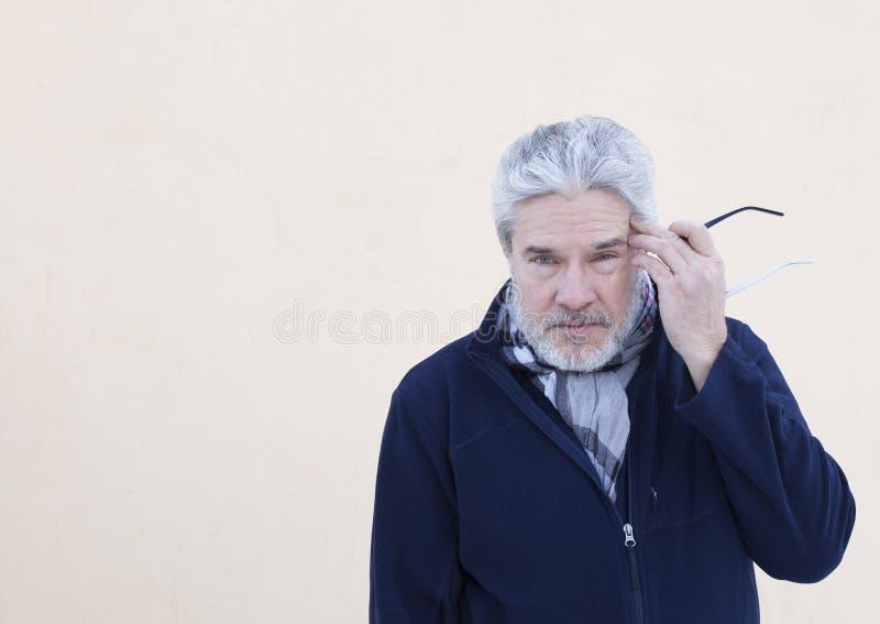 Uomo anziano che tiene i vetri vicino al suo testa fotografie stock libere da diritti