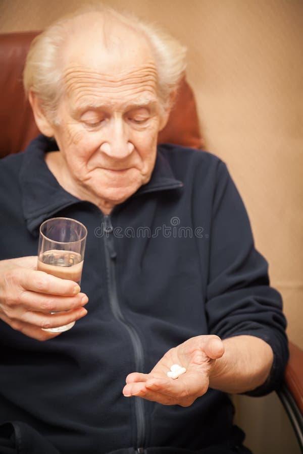 Uomo anziano che tiene un bicchiere d'acqua e le pillole fotografie stock libere da diritti