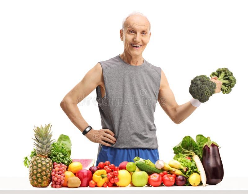 Uomo anziano che tiene una testa di legno dei broccoli dietro una tavola con il frui fotografia stock