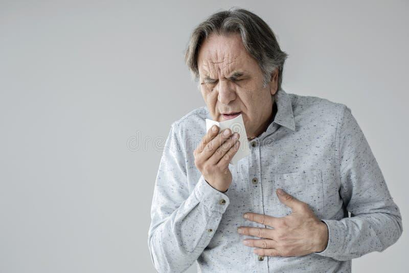 Uomo anziano che tossisce al tessuto fotografie stock