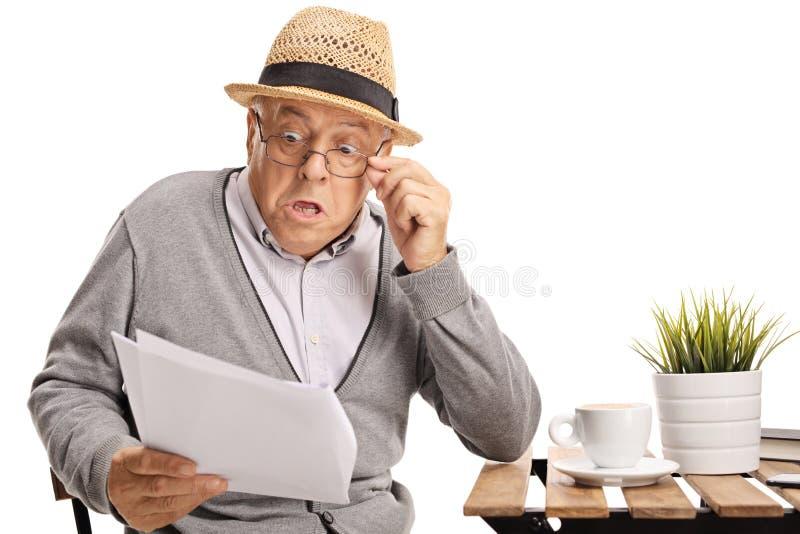 Uomo anziano colpito che legge un documento immagine stock libera da diritti