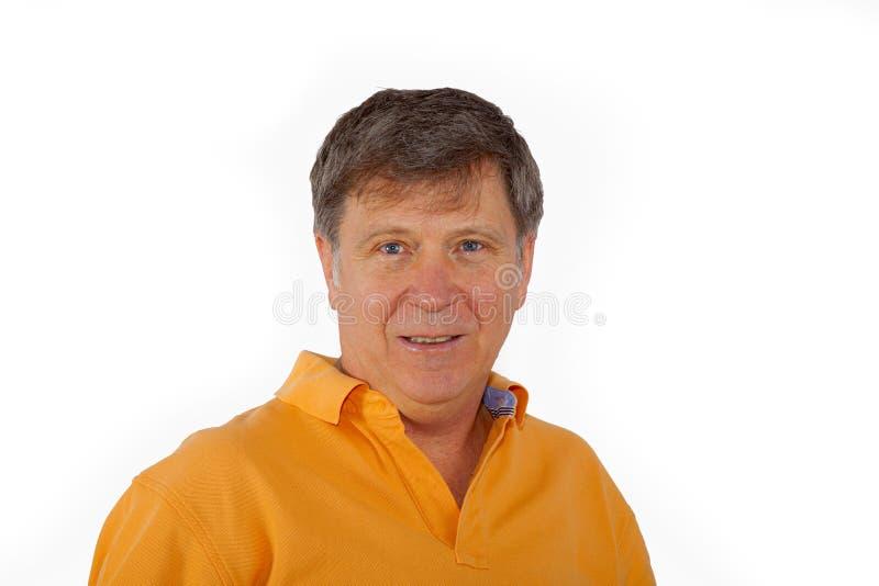 Uomo anziano con camicia arancione che sembra positivo fotografia stock