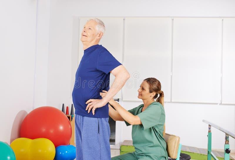 Uomo anziano con dolore alla schiena in fisioterapia fotografie stock libere da diritti
