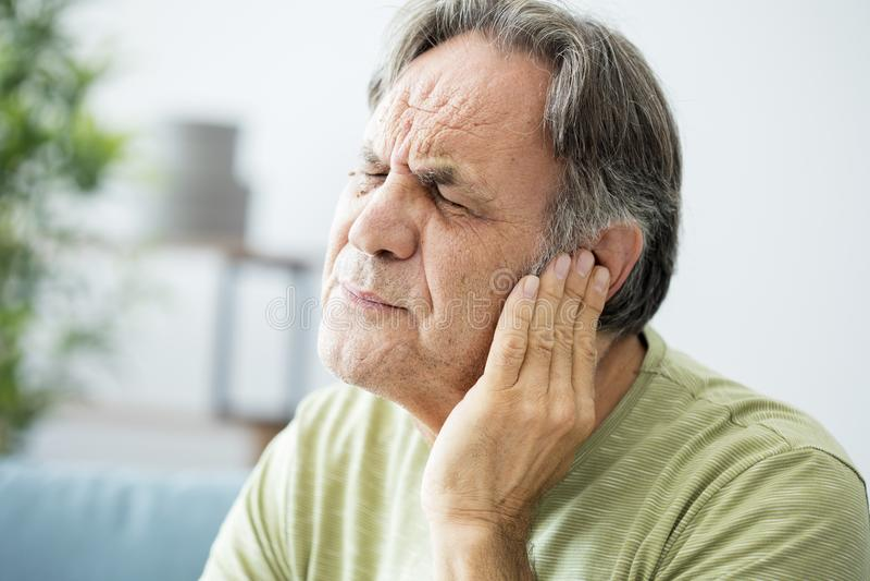 Uomo anziano con dolore di orecchio fotografia stock