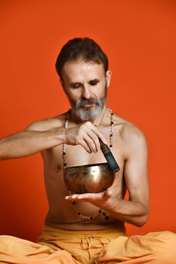 Uomo anziano con gli Yogi grigi di una barba in buona ciotola fisica di canto della tenuta di forma fotografia stock