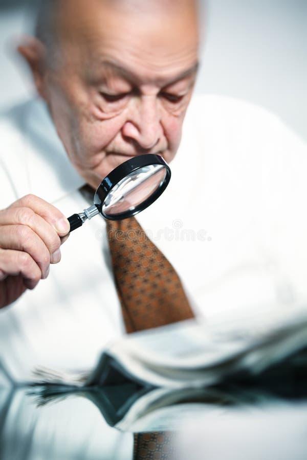 Uomo anziano con il magnifier fotografie stock