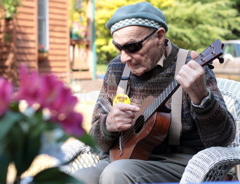 Uomo anziano con il Ukulele immagini stock libere da diritti