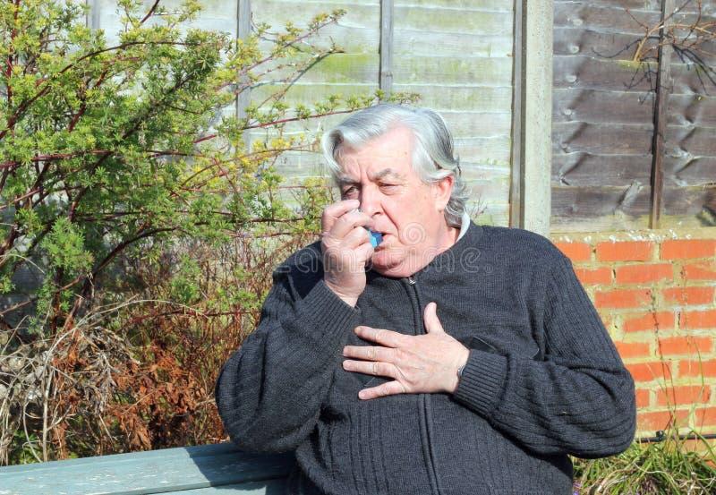 Uomo anziano con l'inalatore di asma. fotografie stock libere da diritti