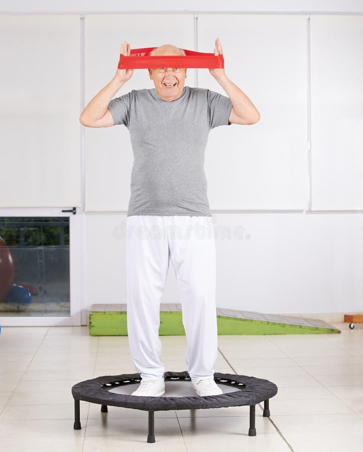 Uomo anziano con la banda di esercizio in fisioterapia fotografia stock libera da diritti