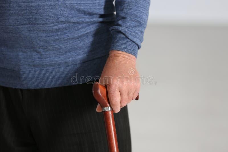 Uomo anziano con la canna di camminata su fondo vago, primo piano della mano fotografia stock libera da diritti