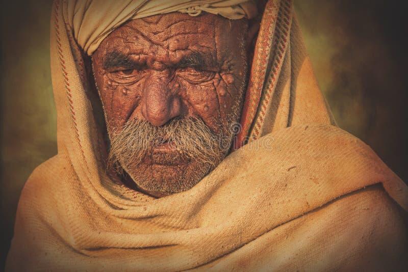Uomo anziano di Rajasthani contro lo sfondo dei suoi cammelli immagine stock