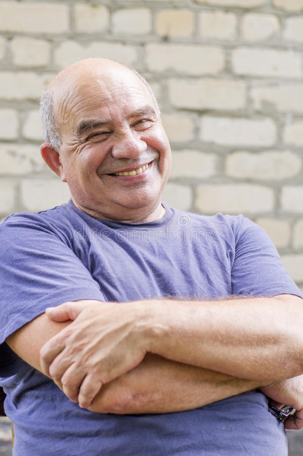 Uomo anziano di risata con le sue armi attraversate fotografie stock libere da diritti