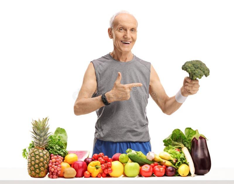 Uomo anziano dietro una tavola con frutta e le verdure che tengono bro fotografie stock