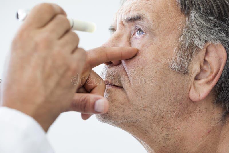 Uomo anziano esaminato da un oftalmologo fotografia stock libera da diritti