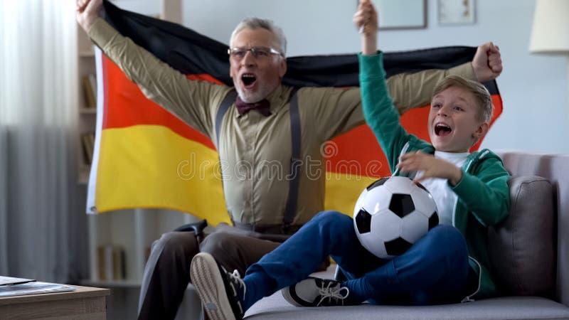 Uomo anziano estremamente felice e ragazzino che celebrano vittoria della squadra di calcio tedesca fotografia stock