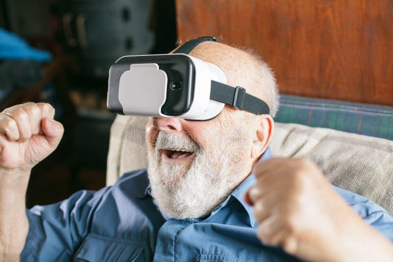 uomo anziano felice che usando gli occhiali di protezione di realtà virtuale a casa fotografie stock libere da diritti