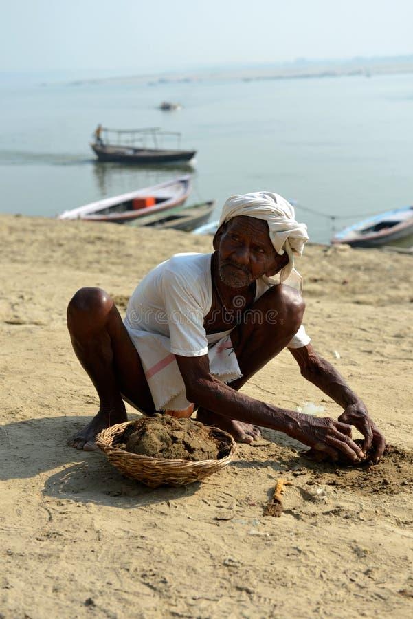 Uomo anziano indiano che raccoglie la merda della mucca fotografia stock libera da diritti