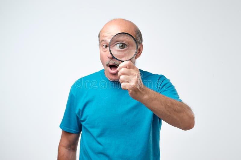 Uomo anziano in maglietta blu che guarda tramite una lente d'ingrandimento Concetto di controllo di controllo di qualità immagine stock libera da diritti