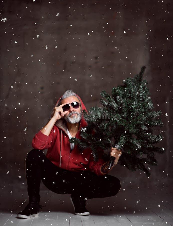 Uomo anziano moderno alla moda di Santa in maglia con cappuccio rossa di modo nell'ambito del Buon Natale della neve fotografia stock libera da diritti
