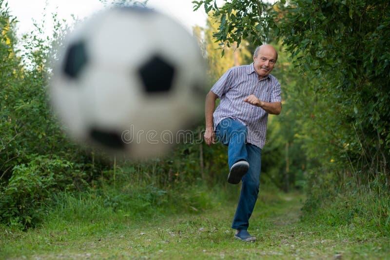 Uomo anziano negli anni settanta che danno dei calci ad un pallone da calcio sul campo da giuoco immagini stock libere da diritti