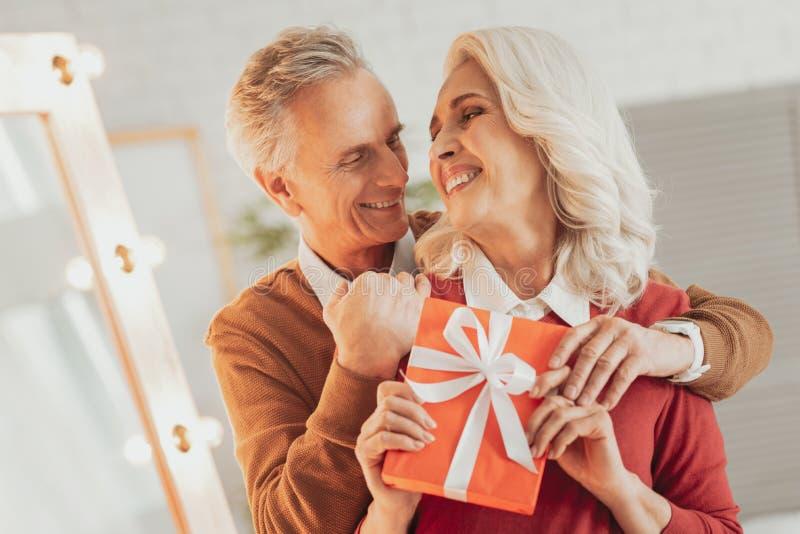 Uomo anziano positivo che abbraccia la sua moglie allegra immagine stock