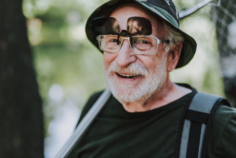 Uomo anziano positivo che sorride alla macchina fotografica fotografia stock
