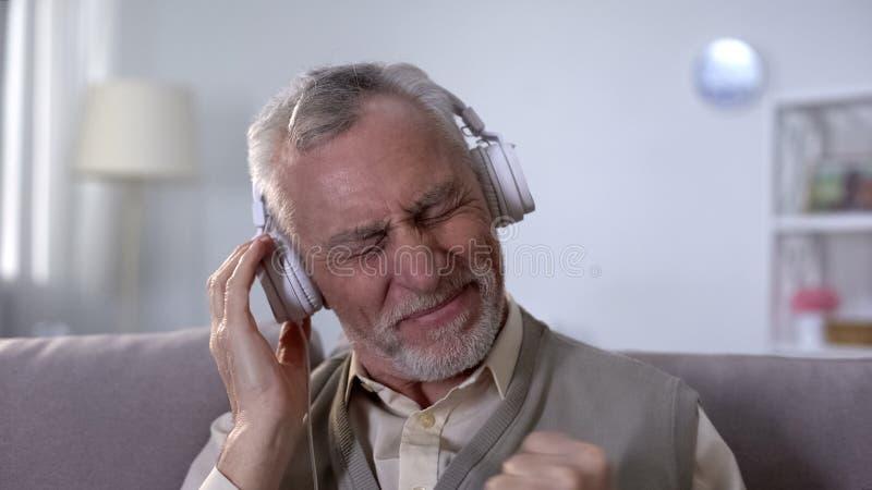 Uomo anziano positivo in cuffie che ascolta per oscillare canzone, di metalli pesanti dalla gioventù immagine stock libera da diritti
