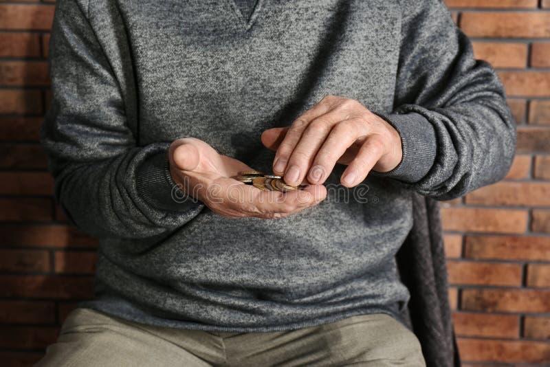 Uomo anziano povero che conta le monete fotografie stock