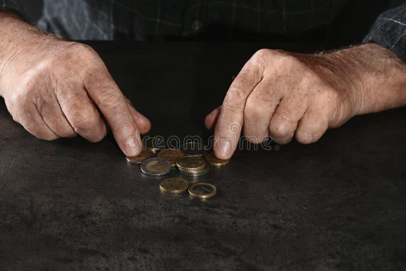 Uomo anziano povero che conta le monete alla tavola fotografie stock
