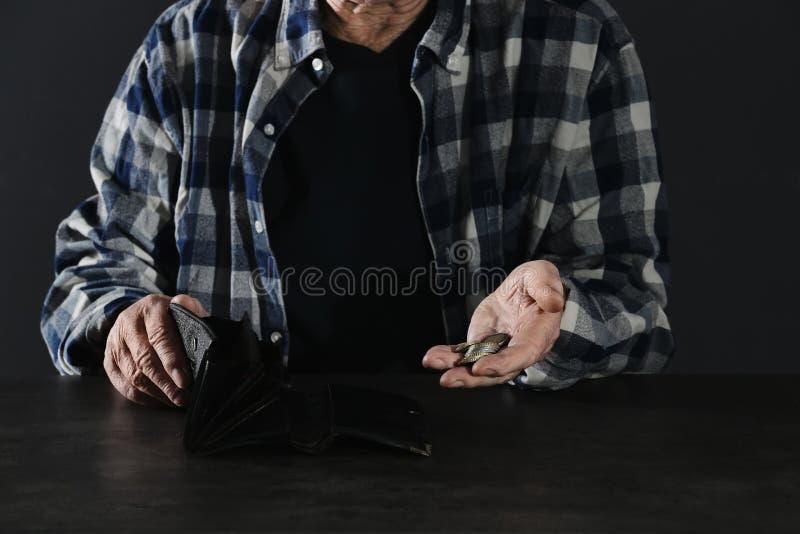 Uomo anziano povero con il portafoglio e le monete vuoti immagini stock libere da diritti