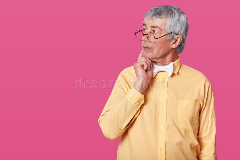 Uomo anziano premuroso con i vetri arrotondati neri sul naso L'anziano anziano guarda da parte e tiene la mano destra sul mento D fotografia stock