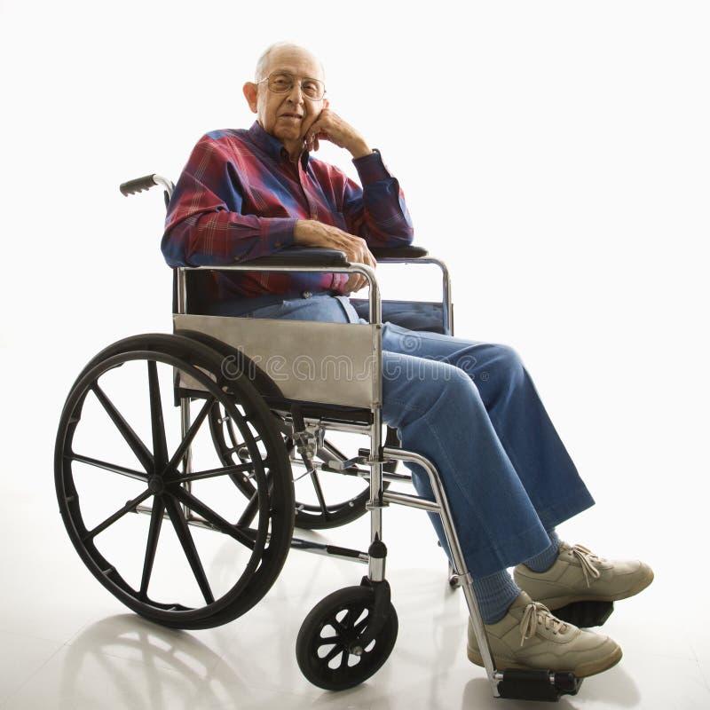 Uomo anziano in sedia a rotelle. fotografie stock