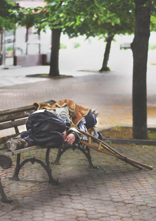 Uomo anziano senza tetto che dorme su un banco immagini stock