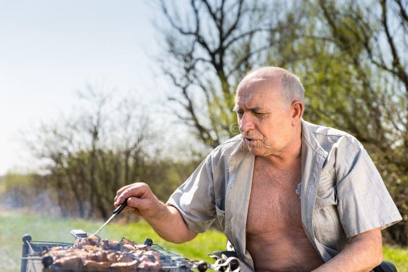Uomo anziano serio che griglia all'area di campo fotografia stock libera da diritti