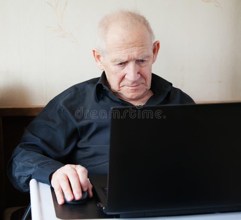 Uomo anziano serio che lavora ad un computer fotografia stock libera da diritti