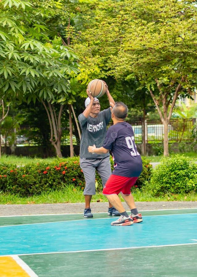 Uomo anziano soddisfatto dell'esercizio giocare pallacanestro al parco di BangYai fotografie stock