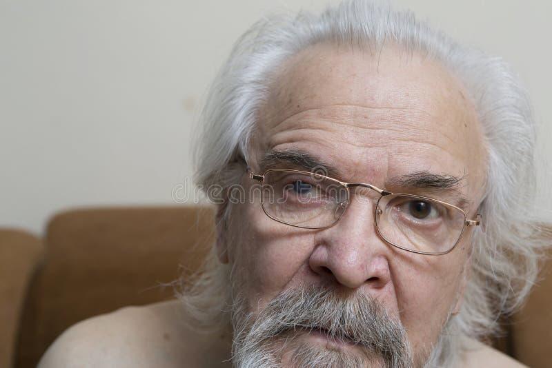 Uomo anziano solo con gli occhi irritati immagine stock