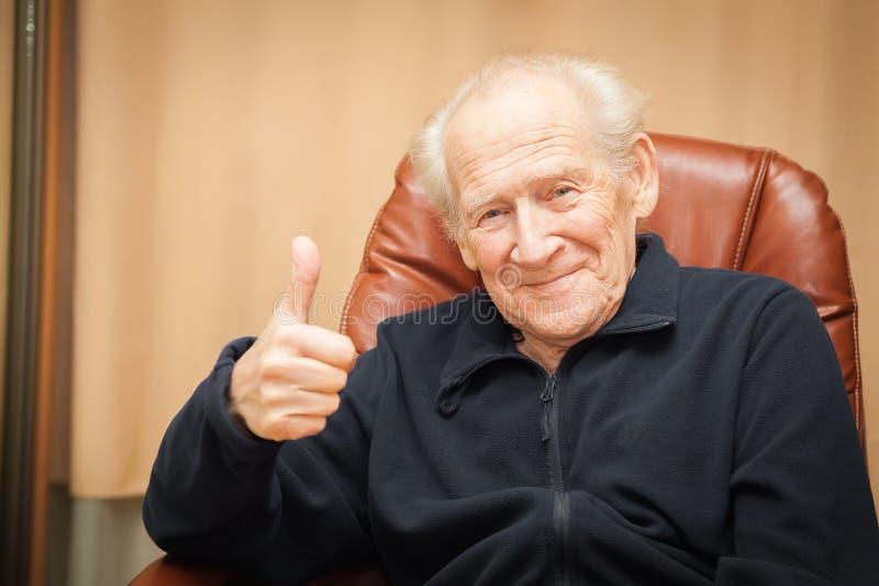 Uomo anziano sorridente che mostra i pollici su fotografia stock